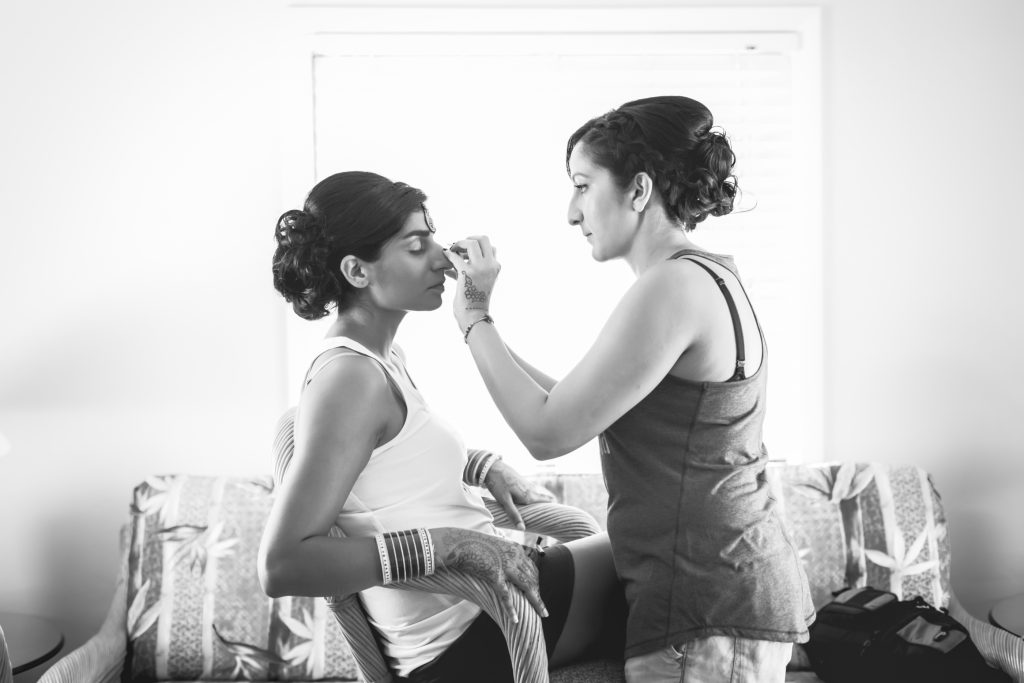 Makeup applies the finishing touches to this beautiful Indian bride before the wedding ceremony in Antigua