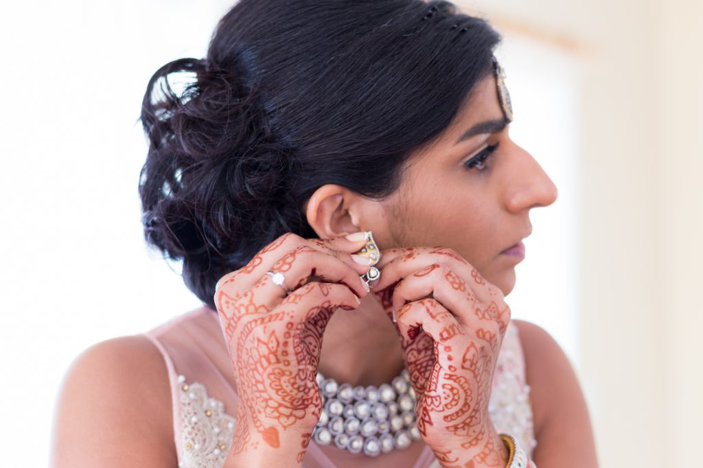 Bride putting on her jewelry and getting ready for the wedding ceremony