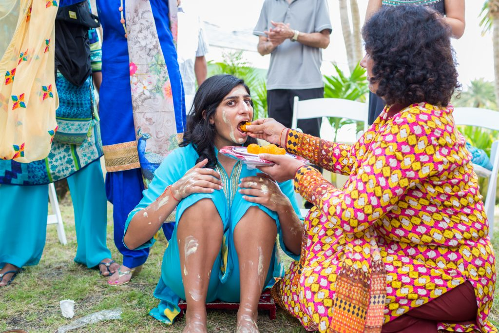 Mother of the bride feeding her daughter during destination wedding Mayian ceremony in Antigua
