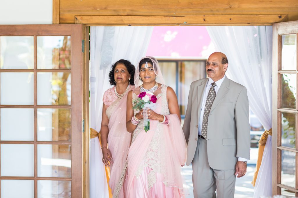 Bride being walked in by both of her parents during their Antigua destination wedding