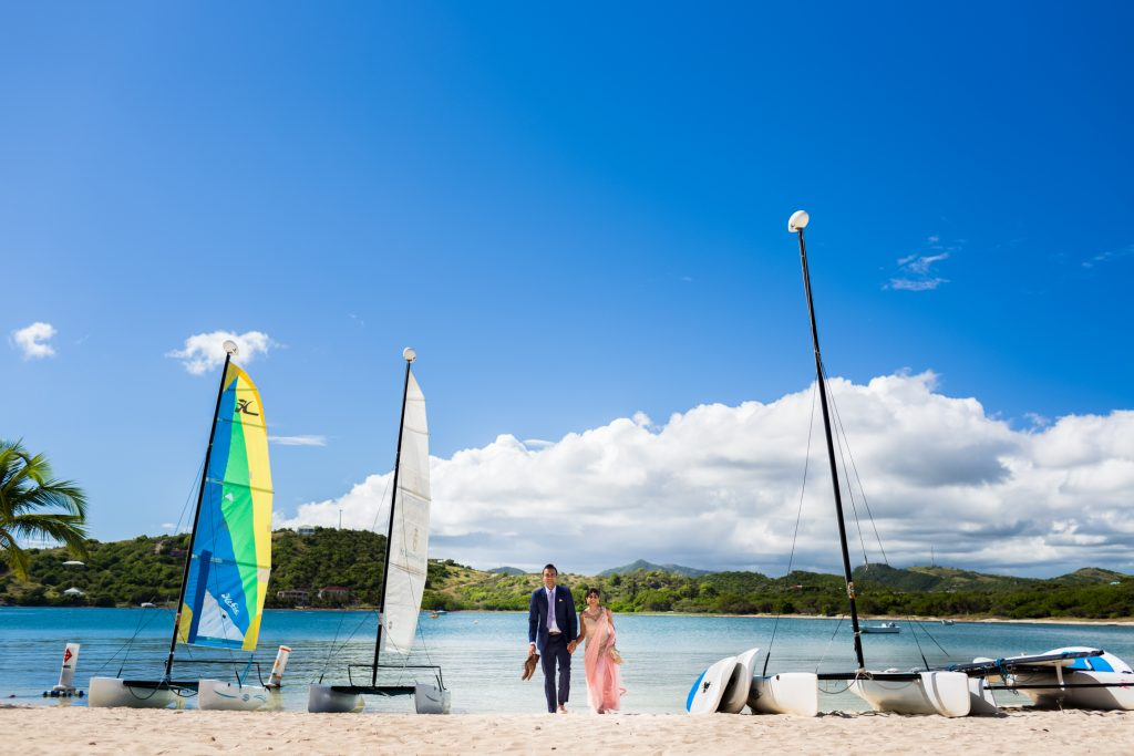 Wedding portraits taken on the beach with sailboats during this beautiful Antigua destination wedding
