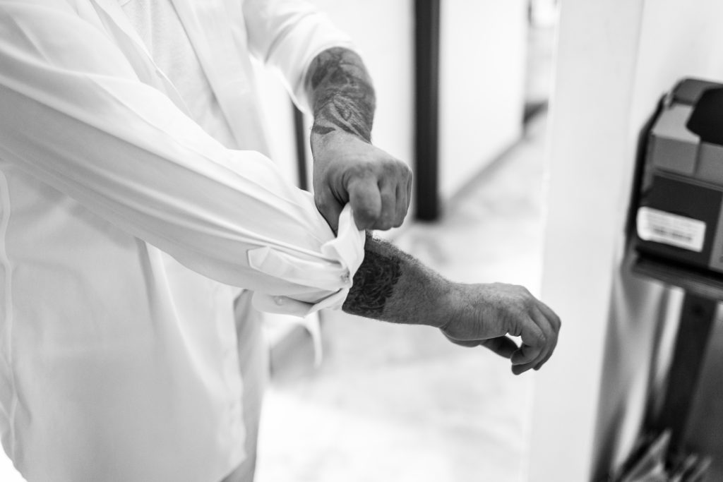 Tattooed Groom putting on his shirt