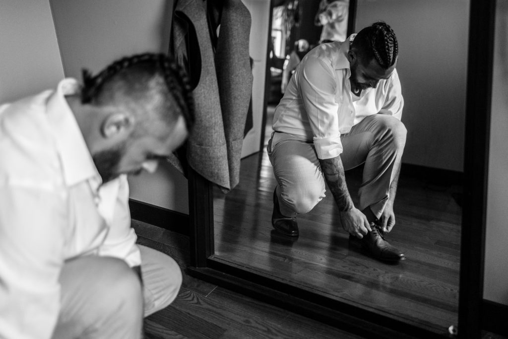Photo of groom putting his shoes on