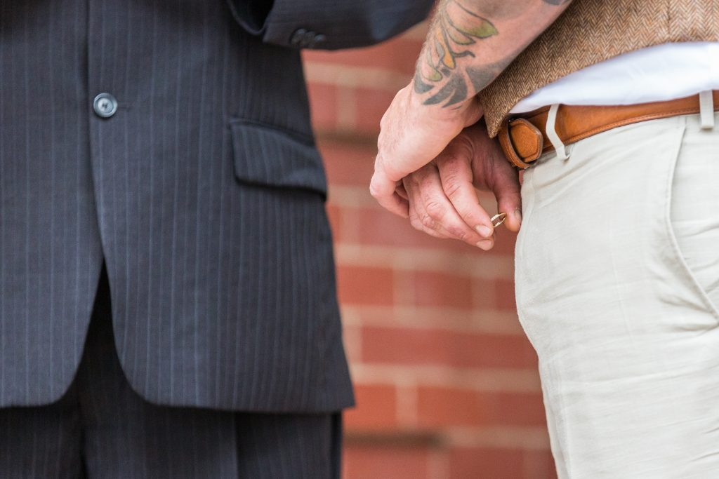 groom holding the brides ring