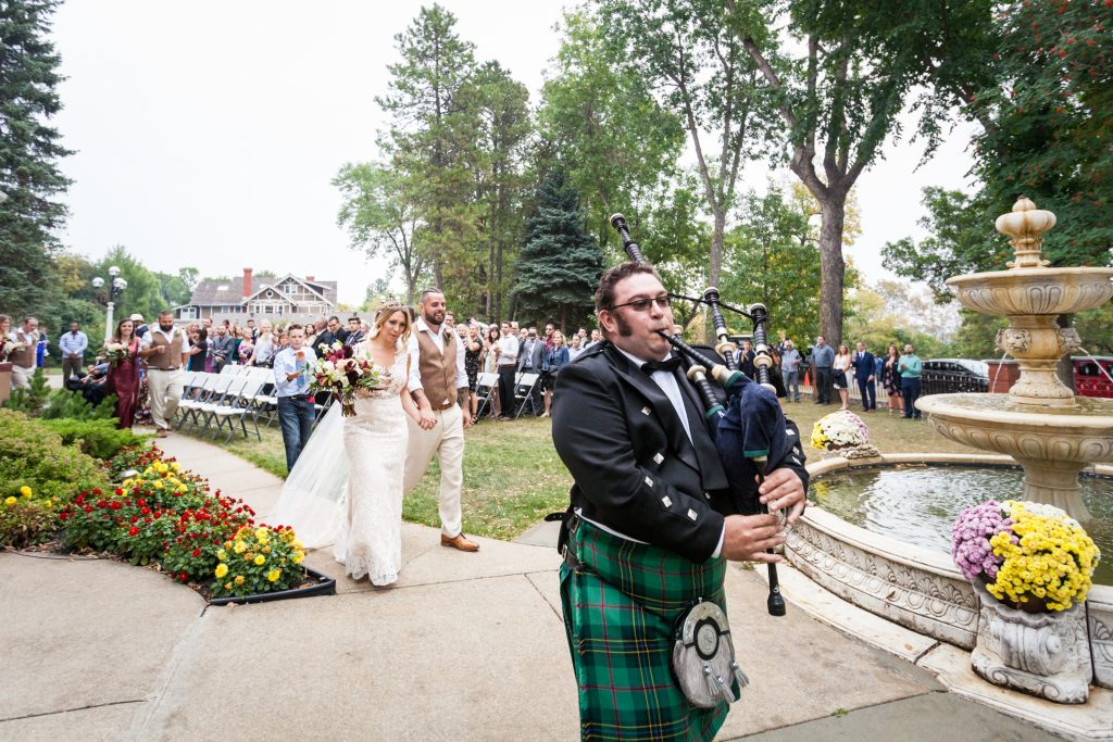 scottish bagpiper leads bride and groom out of ceremony