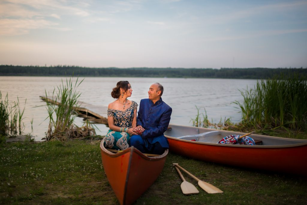 Sunset wedding portrait of the bride and groom sitting in a canoe