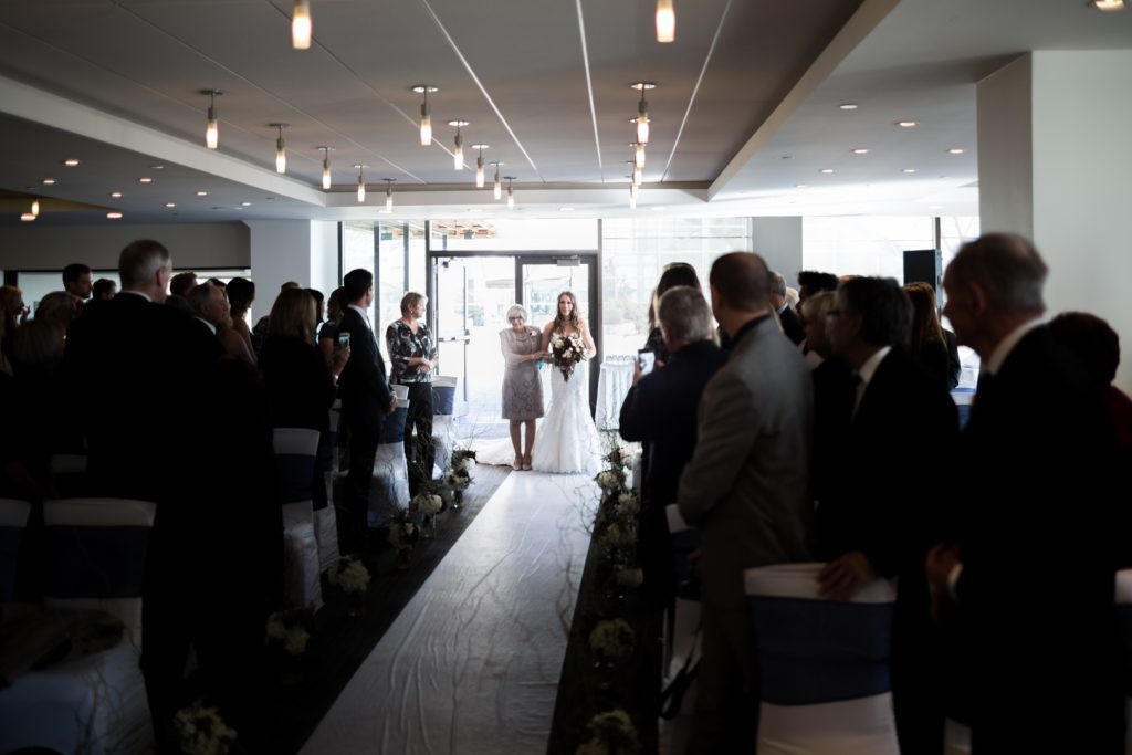 Bride entering the Riverview room for Shaw Conference Centre wedding ceremony