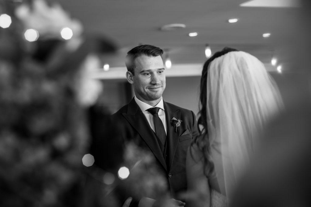 Groom looking at his bride during Shaw Conference Centre wedding ceremony