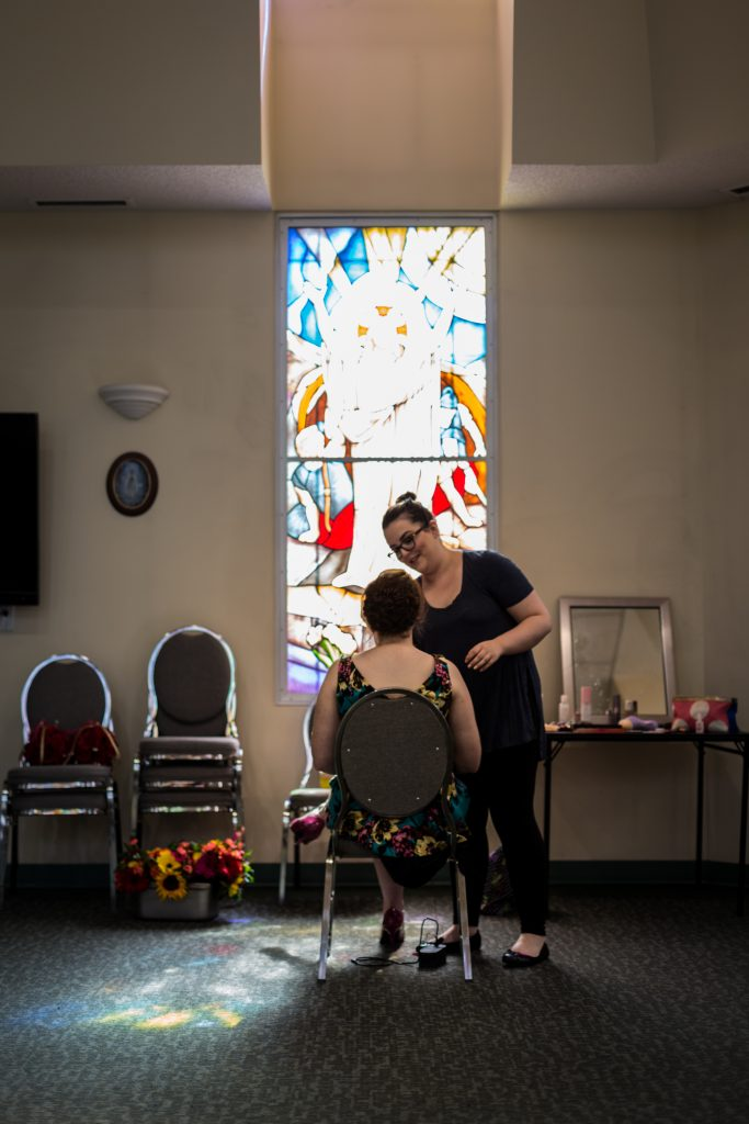 Bride getting her hair done at St Thomas More Church before the wedding ceremony