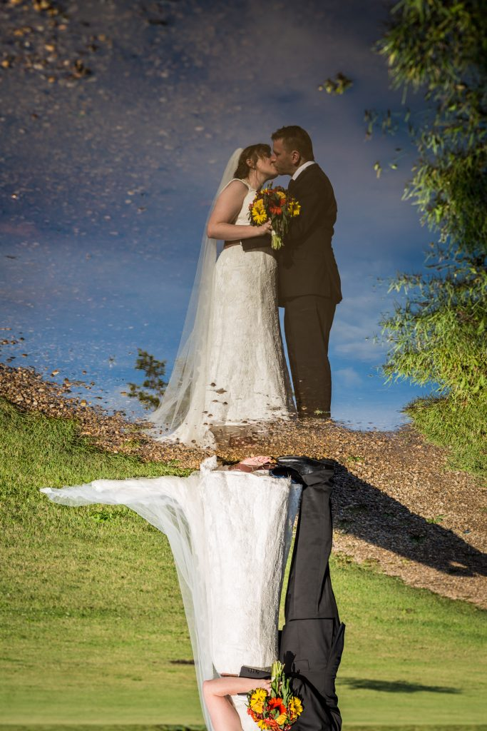 Reflection photo of the bride and groom kissing taken after their wedding at St Thomas More Church