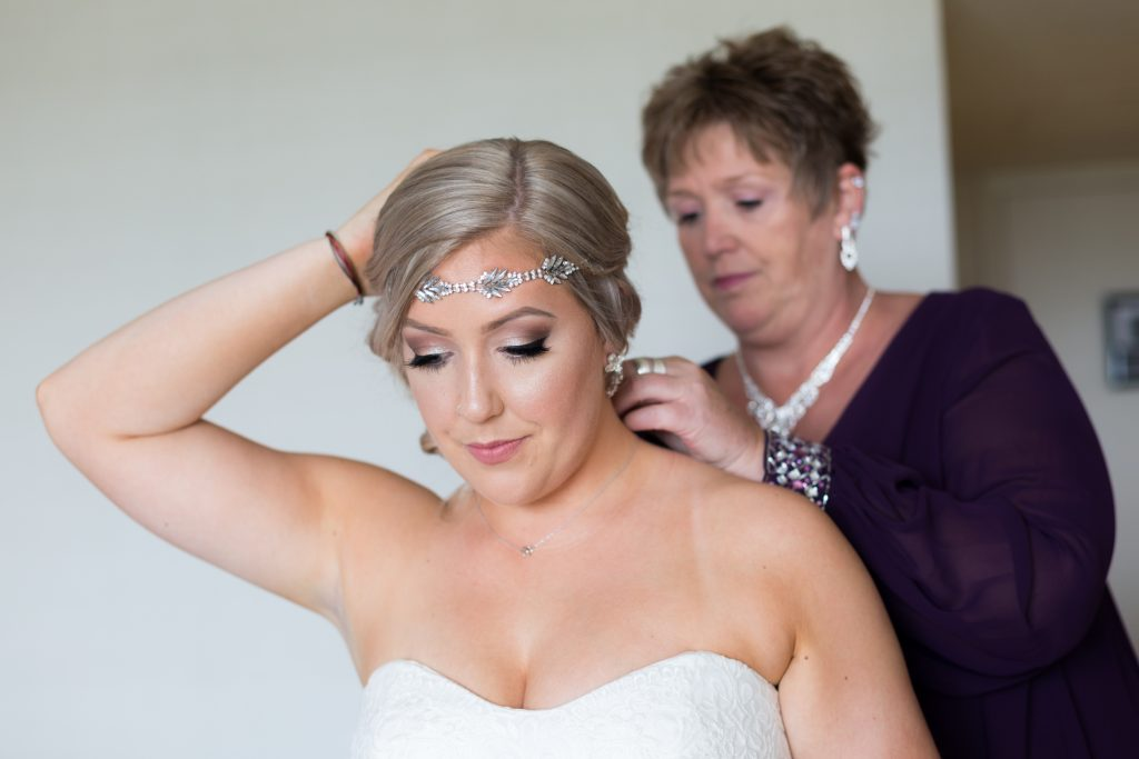 Mother of the bride helping her daughter with her jewelry before the wedding ceremony at Snow Vally