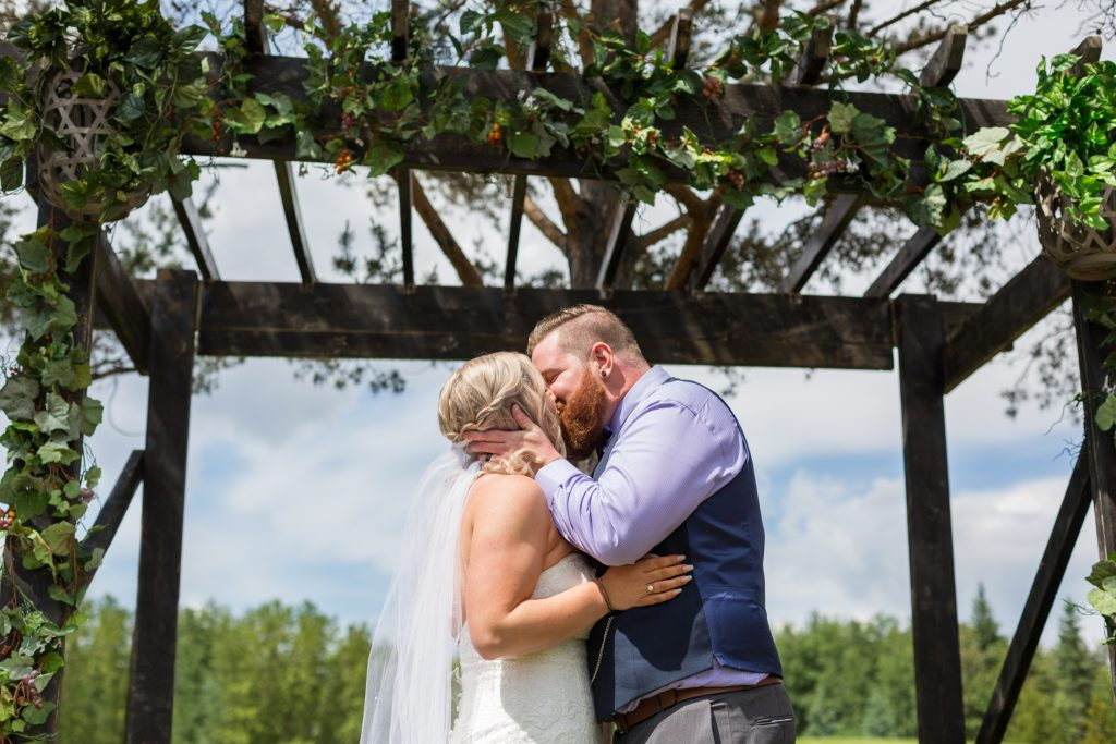 First kiss between the bride and groom during their outdoor summer wedding at Snow Valley
