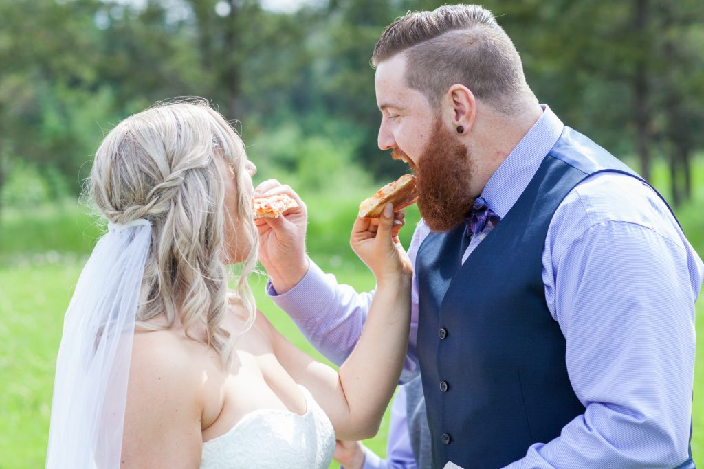 Bride and groom feed each other pizza during their portrait session at Snow Valley