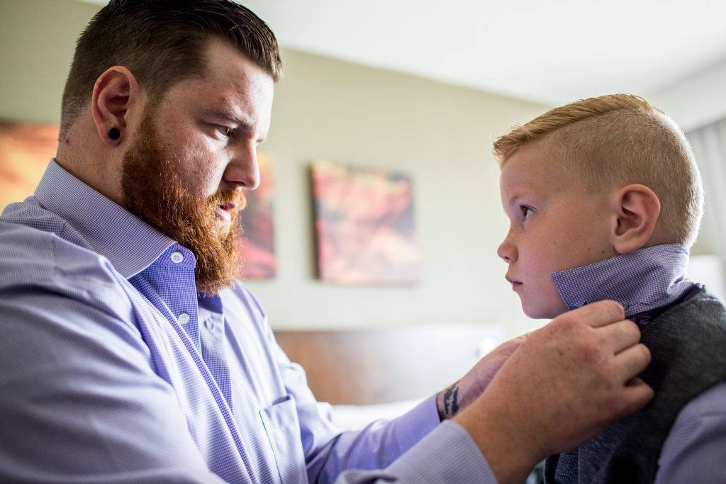 Groom helps his son with his tie before heading to Snow Valley for wedding ceremony