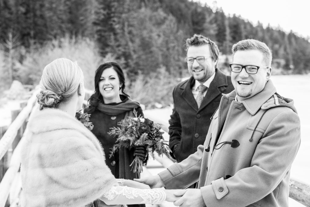 Candid photo of the wedding party greeting the bride and groom after their first look on the bridge to Pyramid Lake island