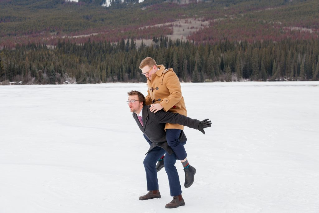 Groom and best man having some fun before the outdoor winter wedding ceremony at Pyramid Lake