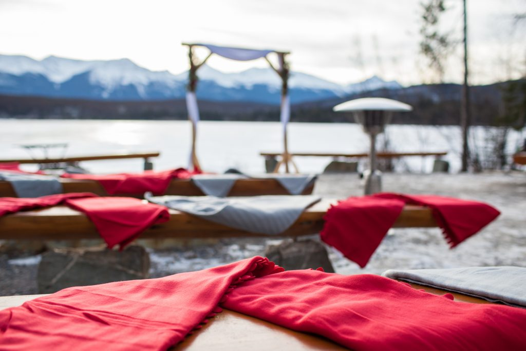 Blankets were set out on the benches for guests during this outdoor winter wedding at Pyramid Lake island