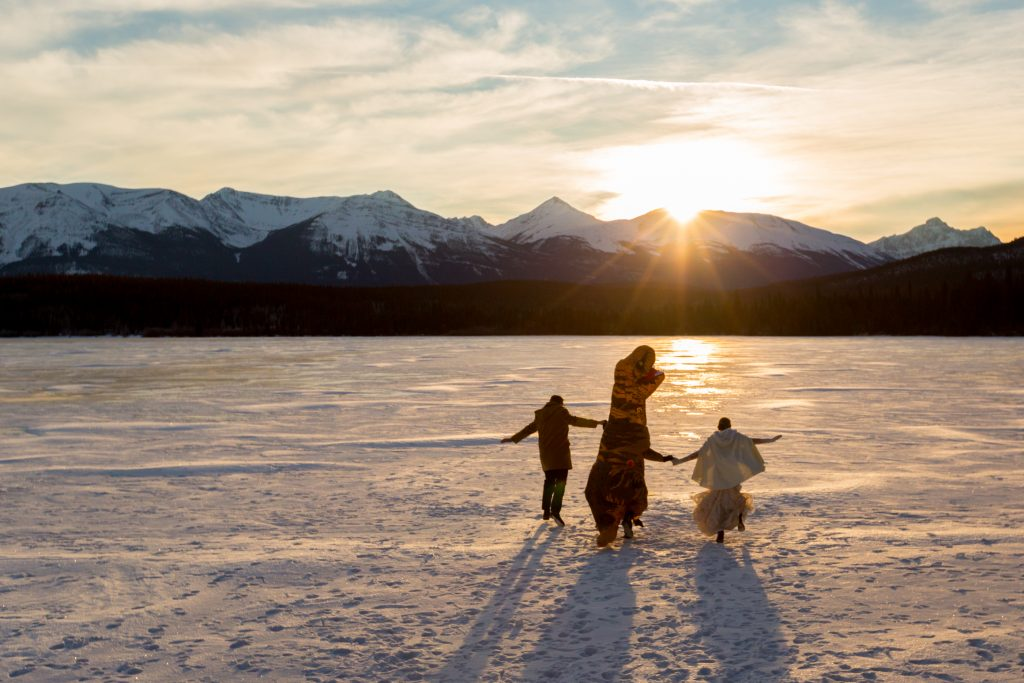Bride and groom run off into the sunset with a giant t-rex during their Pyramid Lake winter wedding