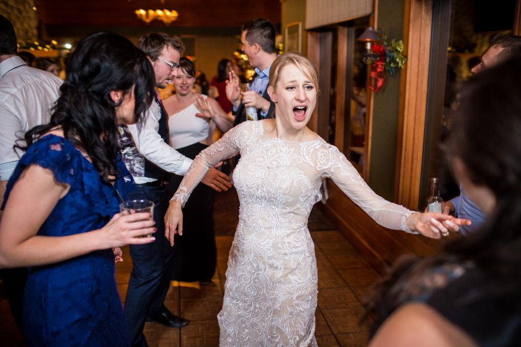Bride dancing with her guests during indoor winter wedding reception at Pyramid Lake Resort