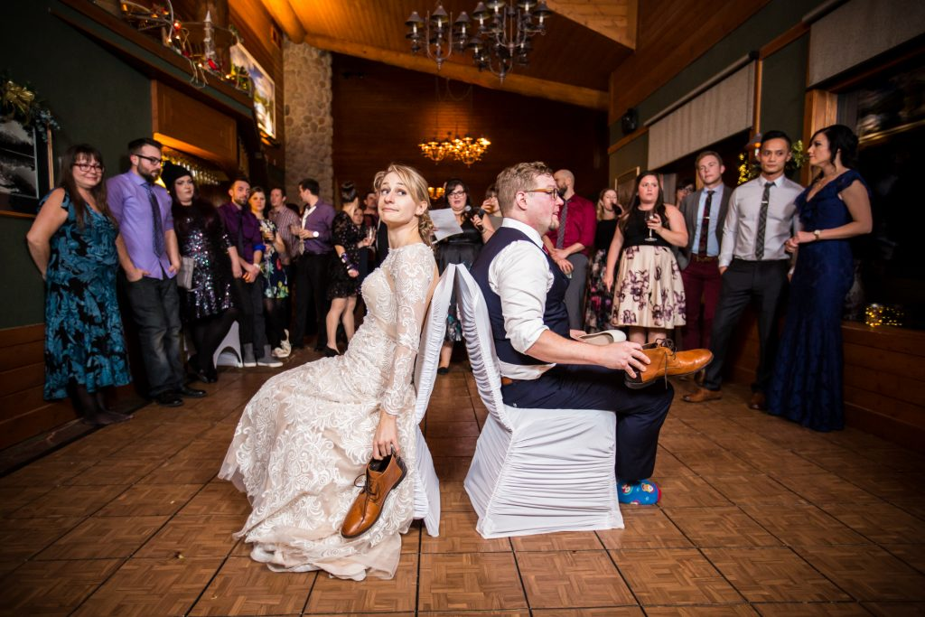 Bride and groom playing the shoe game during their winter wedding in Jasper