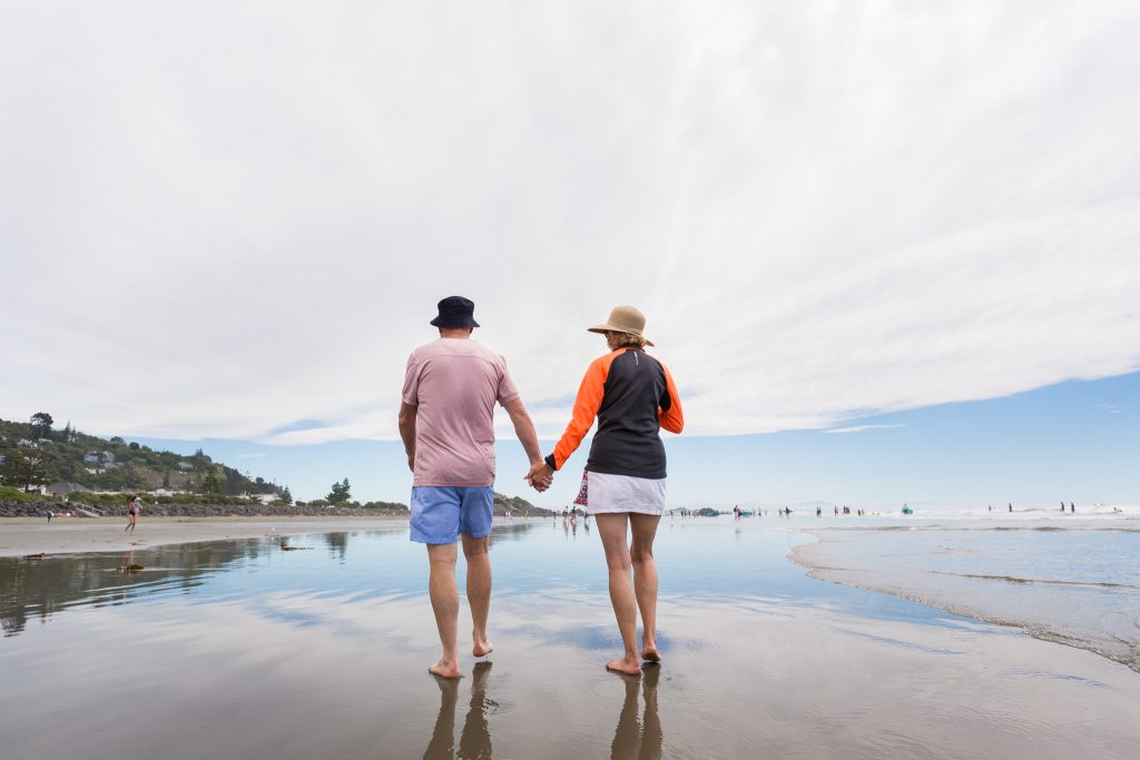 couple holding hand walking down the beach