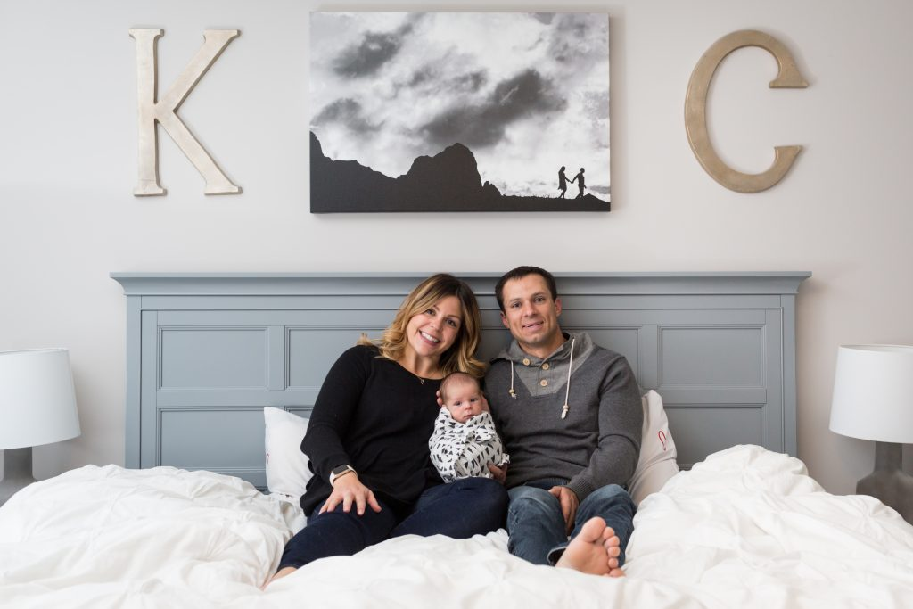 Newborn Family Portraits of parents snuggling in bed with their son
