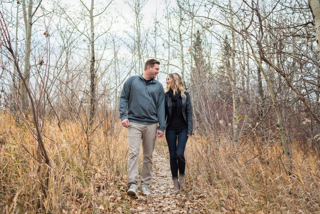 Couple walking through the autumn leaves during their Strathcona science park engagement photos