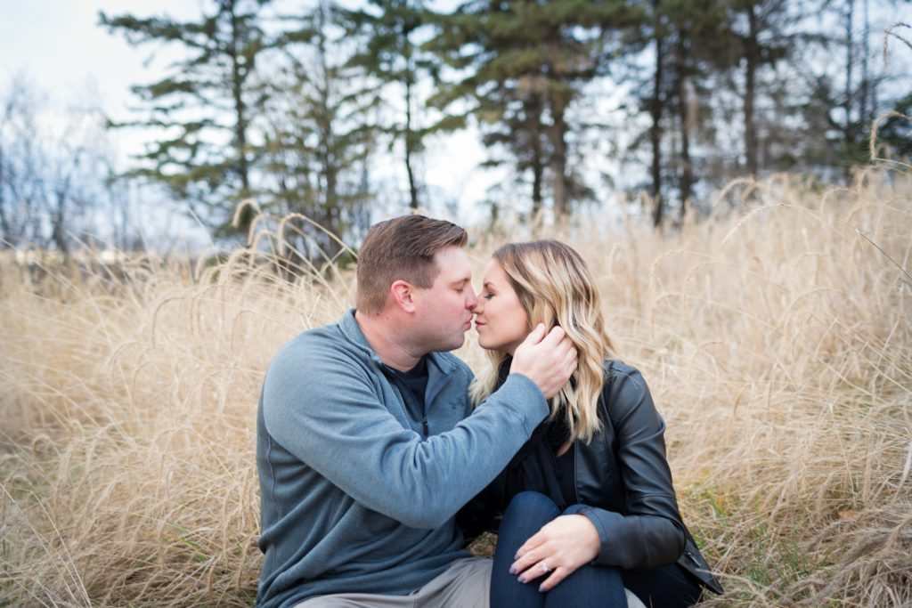 Couple sitting in the tall grass during their Strathcona science park engagement photos