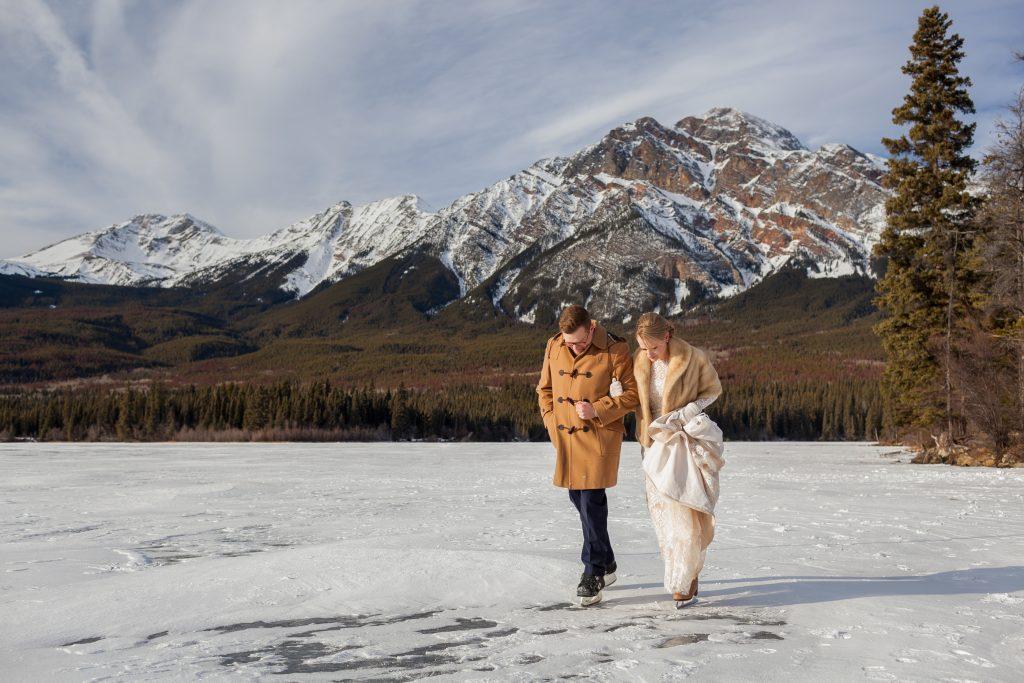 Bride and groom skating on ice mountain winter wedding