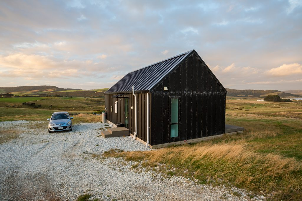 picture of the little black barn overlooking curio bay