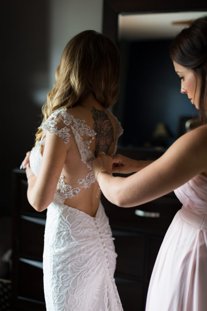 Detail of bride putting on wedding dress
