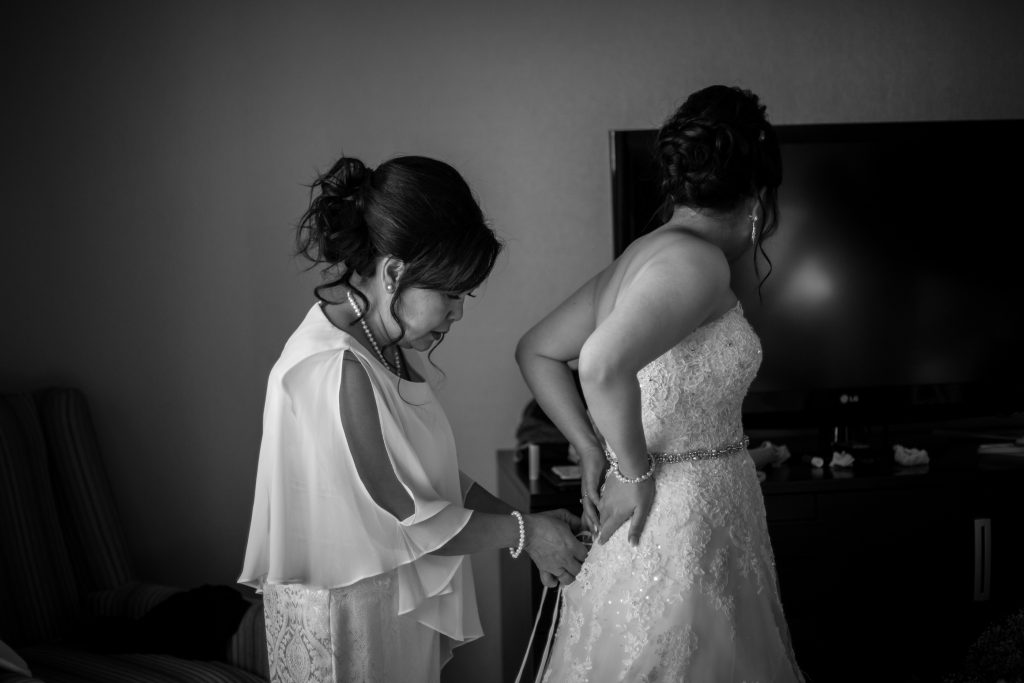 mother of the bride helping with wedding dress