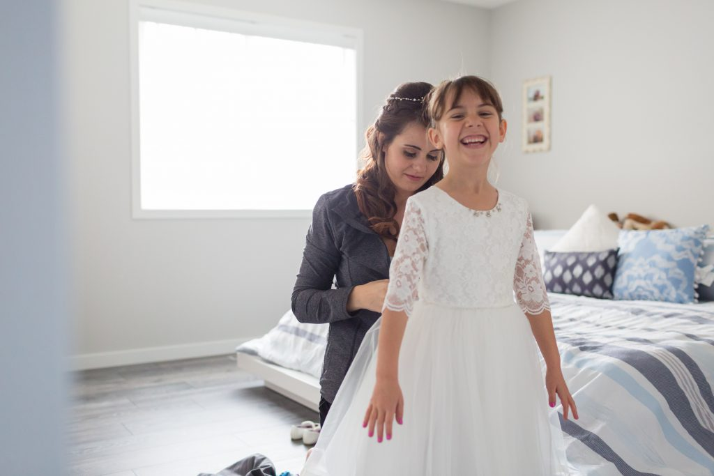 bride helping flower girl get ready
