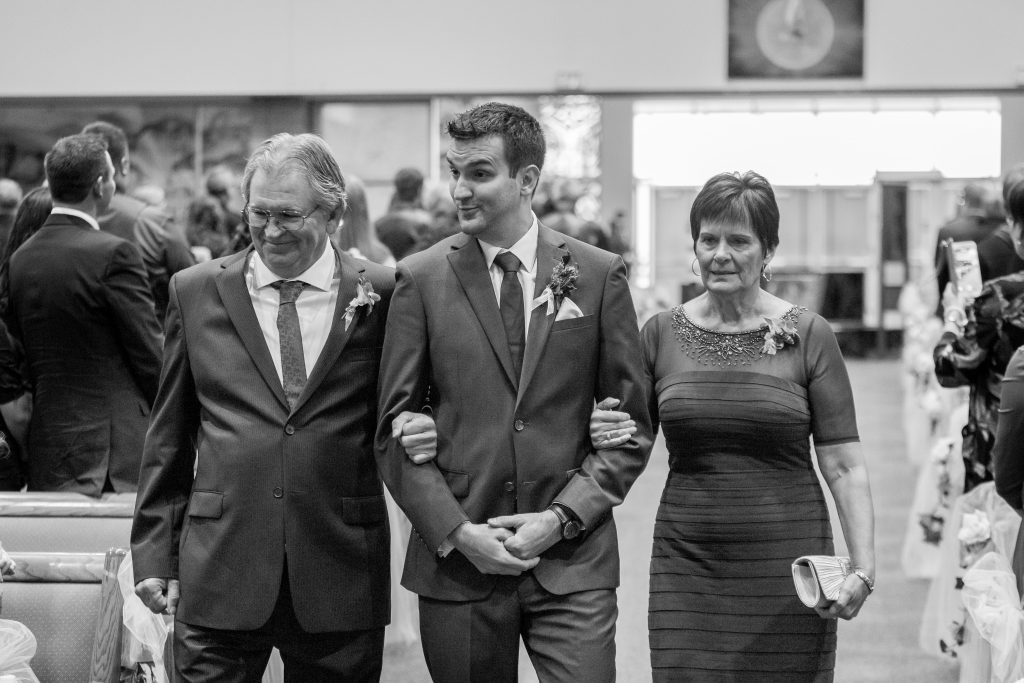 Groom being walked down aisle by his parents