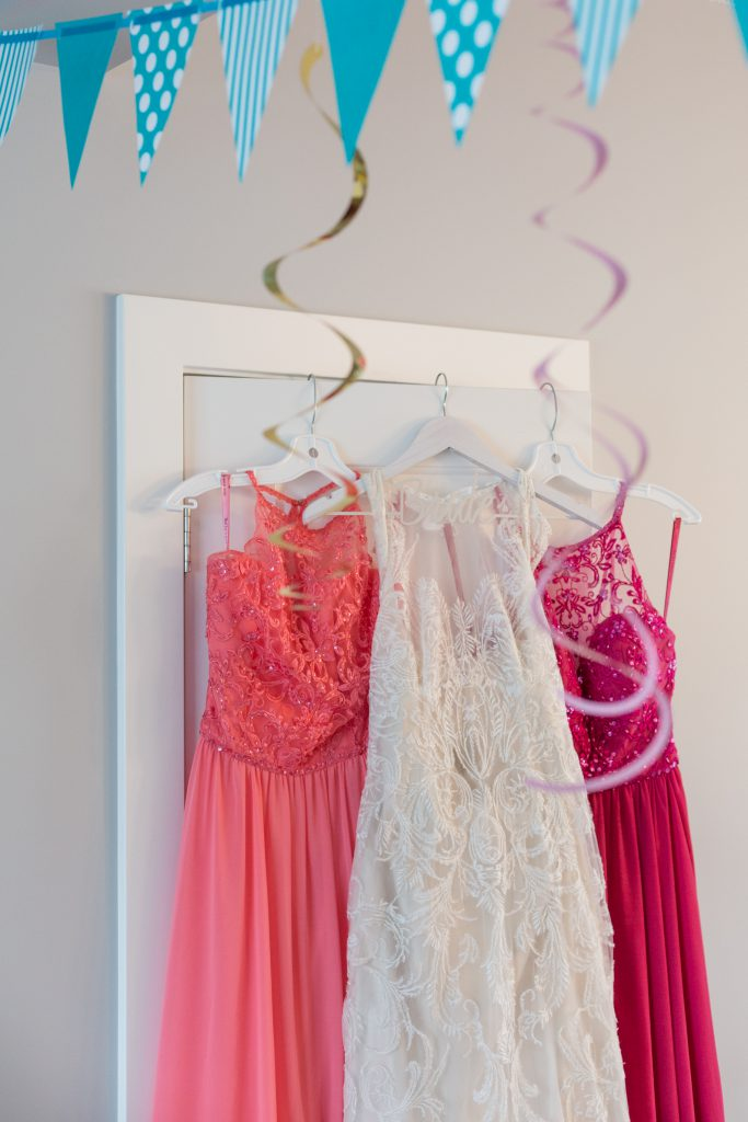 Wedding dress hanging with bridesmaids dresses