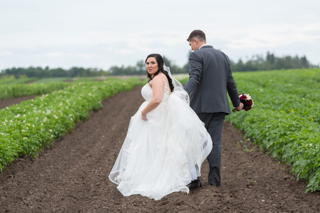 country bride and groom walking through field